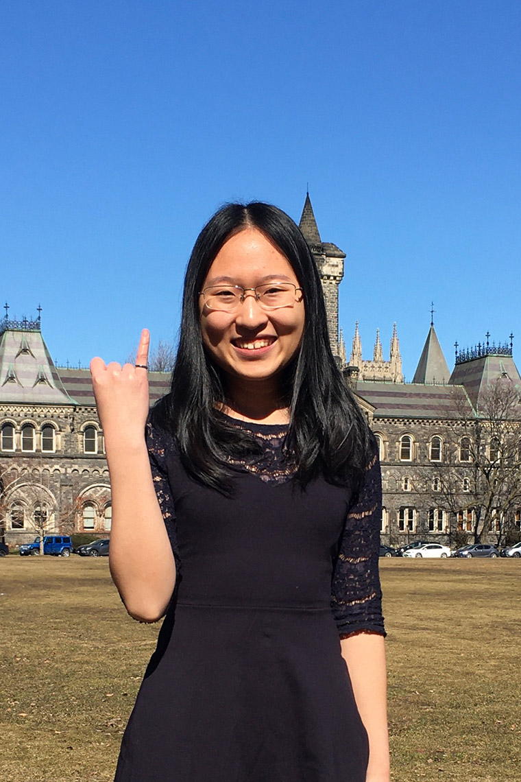 Maddy zhang holds up her showing her iron ring while posing in front of University College