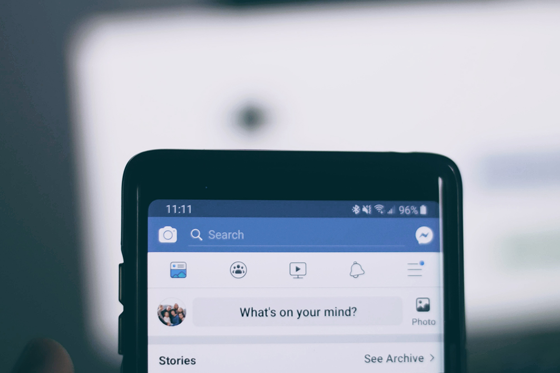 "close up of smartphone with facebook app up. Text on screen reads ""what's on your mind?"""