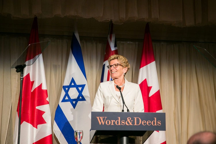 Ontario Premier Kathleen Wynne stands in front of Canadian and Israel flags