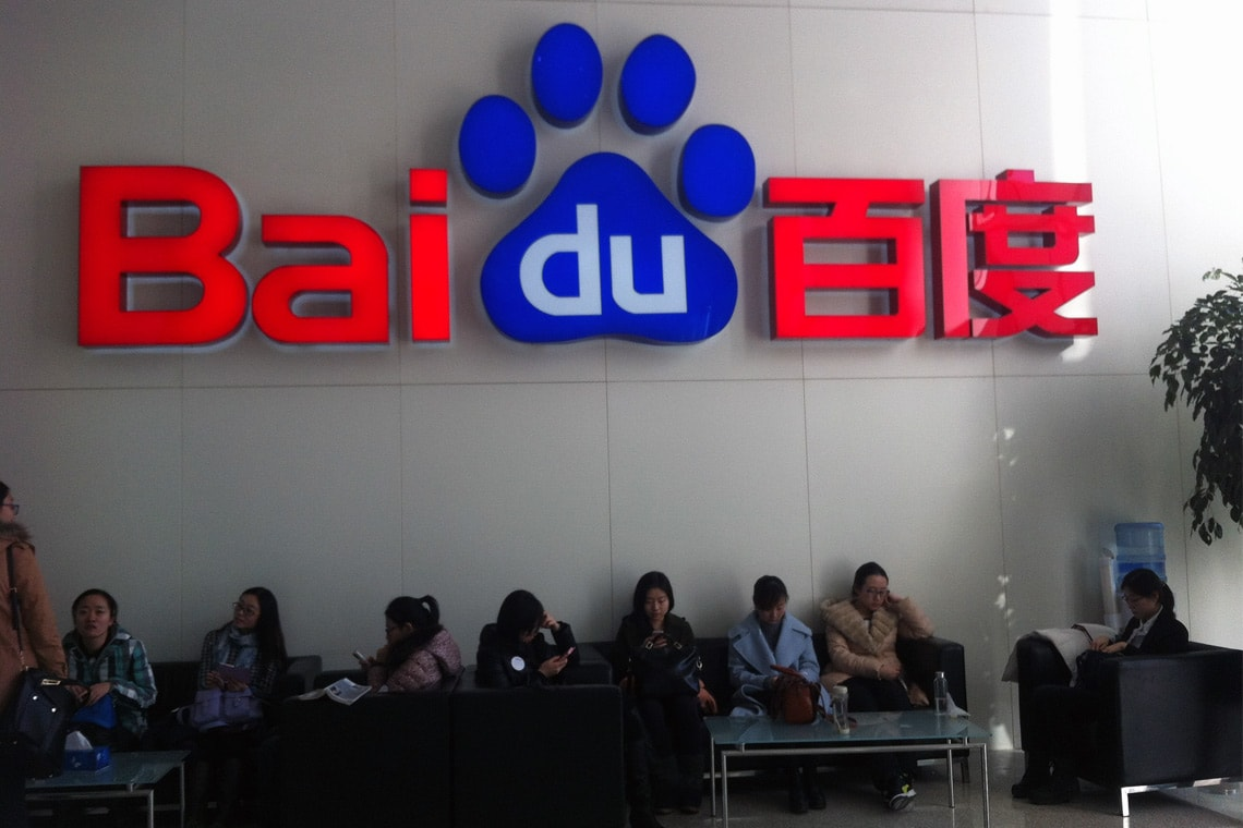 Photo of people sitting underneath a Baidu sign