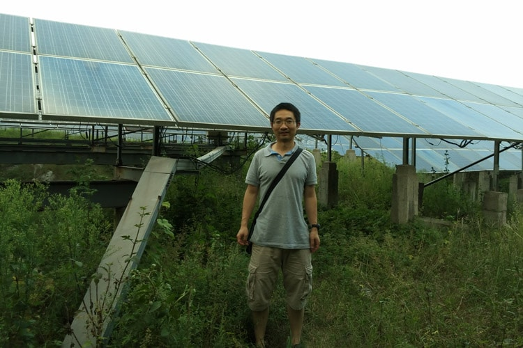 Cheng Lu stands in front of a solar panel factory