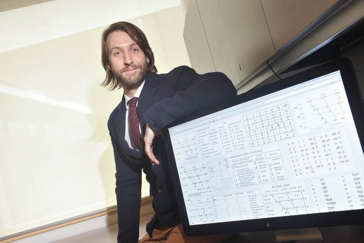 Professor Sam Maglio poses with his computer screen
