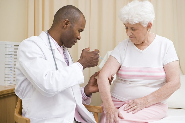 Photo of doctor giving needle to patient
