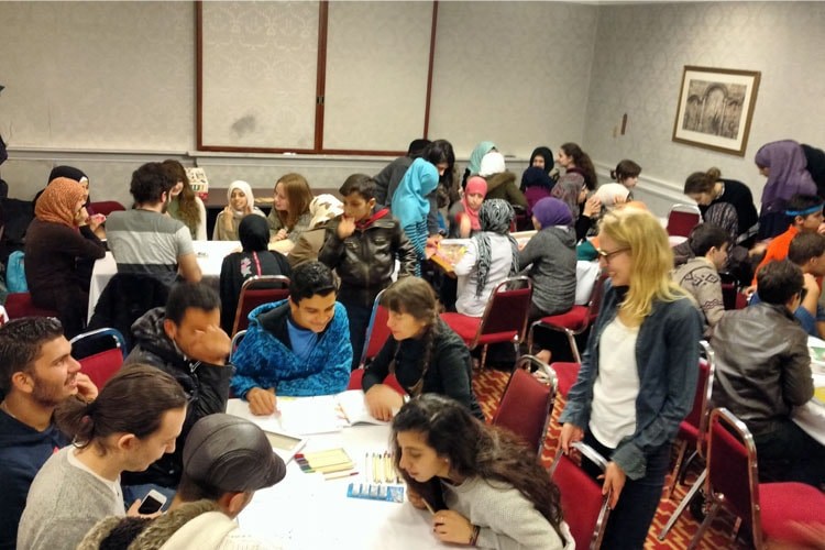A group of youth working around tables and working together at a workshop