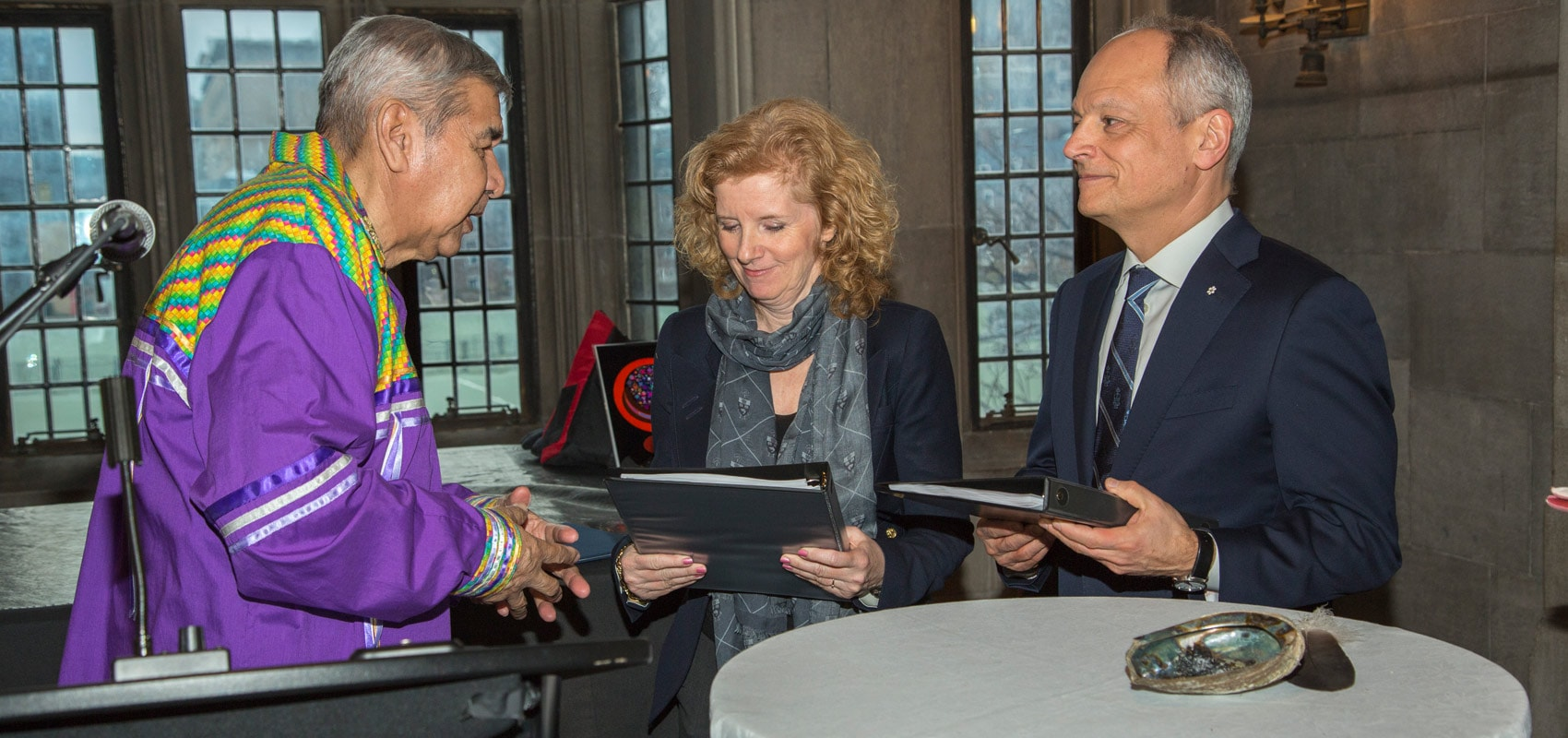 Elder Andrew Wesley (left) presents U of T's Truth and Reconciliation Steering Committee's final report to Provost Cheryl Regehr (centre) and President Meric Gertler (right) at Hart House Jan. 13 (photo by Johnny Guatto)