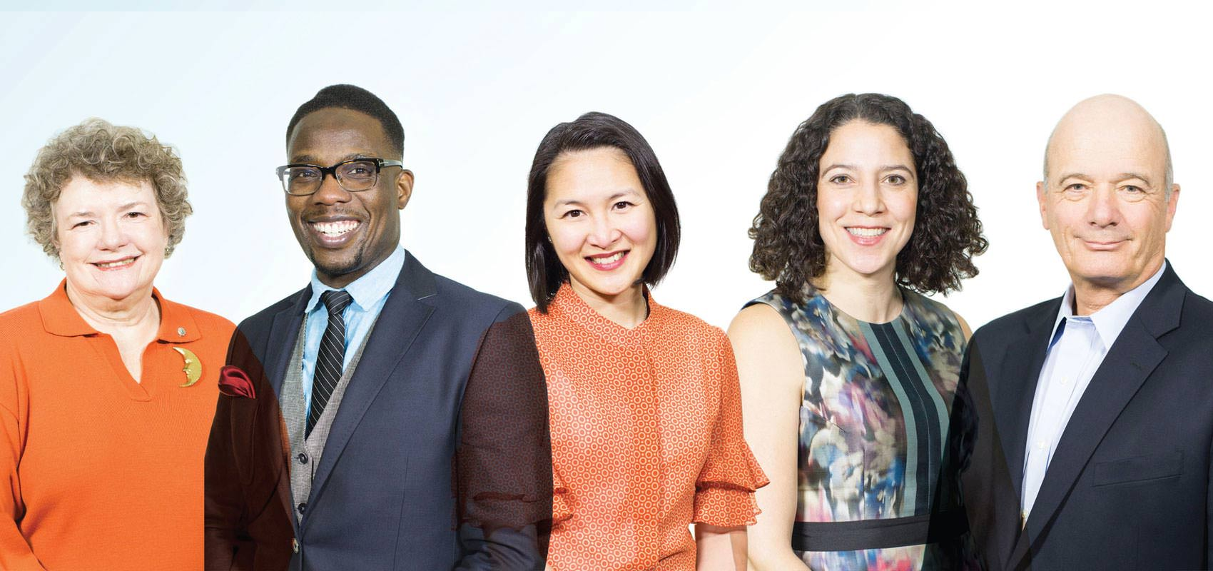 A diverse group of three business women and two business men smiling