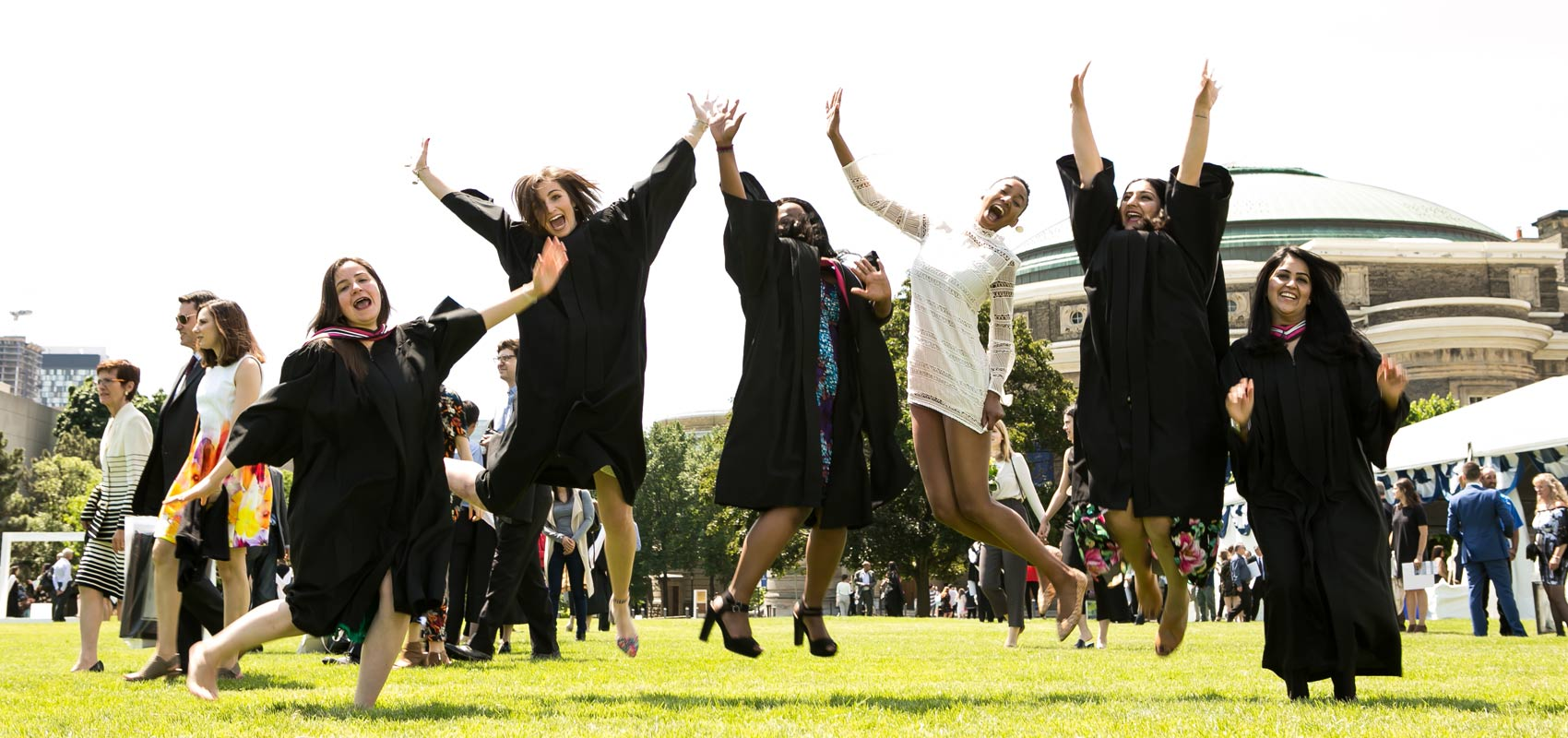 A group of students smiling and jumping in the air at their convocation ceremony on front campus, St. George. Photo credit: Dhoui Chang