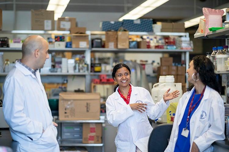 Meena Venkatesan explains something in a lab