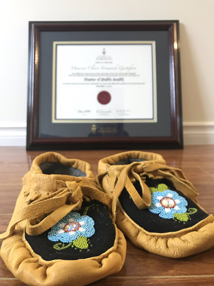 Gustafson's mother's moccasins sit in front of Gustafson's degree