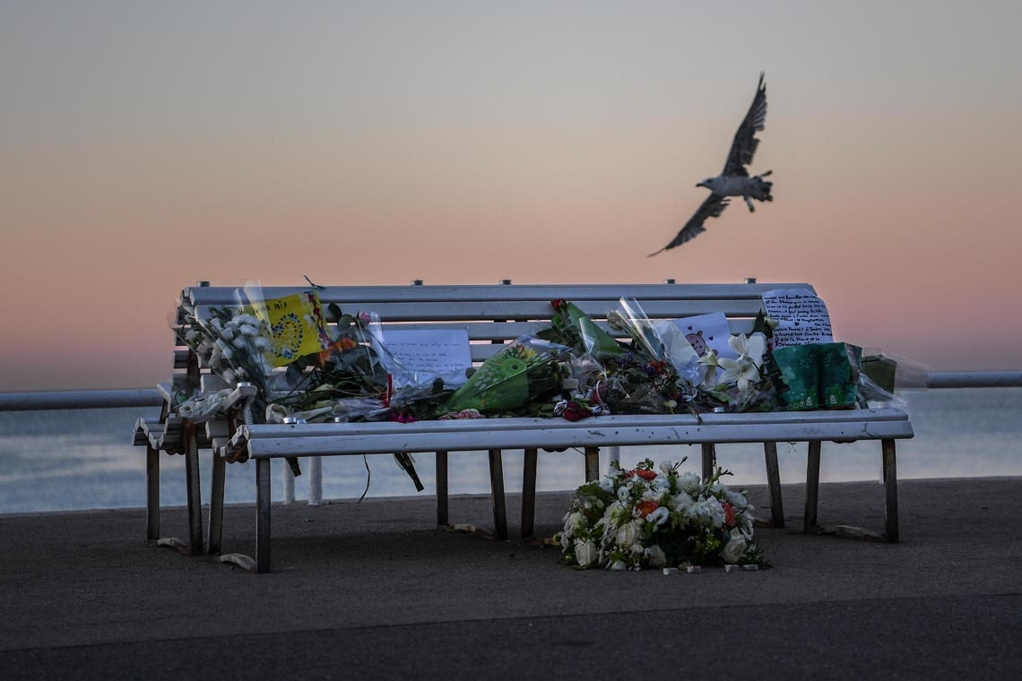 Seagull flies beside bench that bears flower tributes to victims of Nice attack