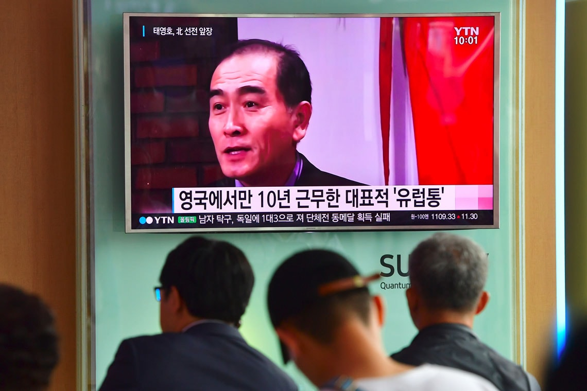 People watch a television news broadcast showing file footage of Thae Yong-Ho, North Korea's deputy ambassador to Britain