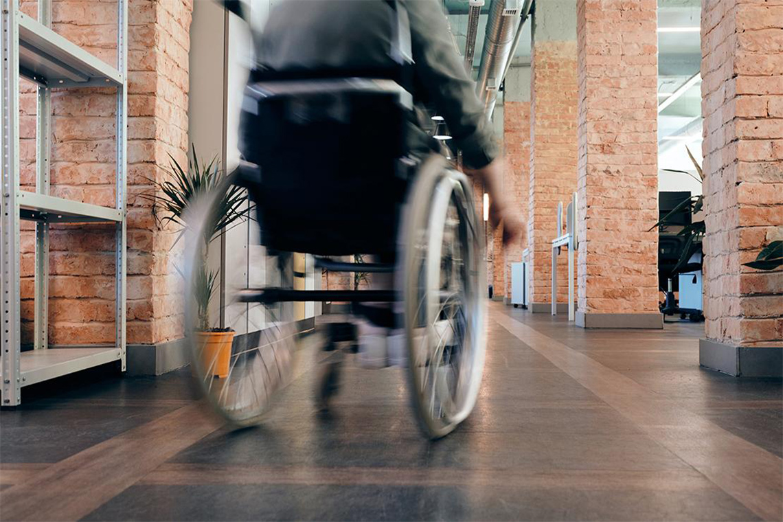 man in wheelchair moves across a room