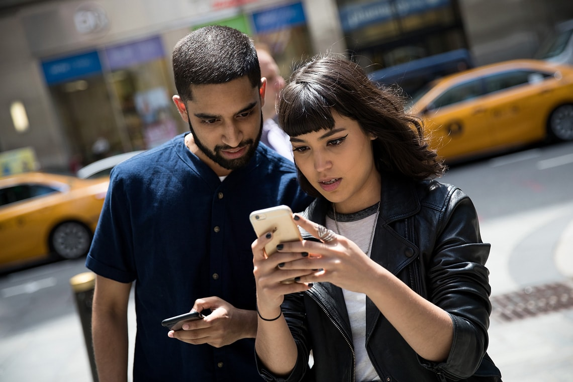 Two people playing Pokémon GO outside the Nintendo flagship store in New York