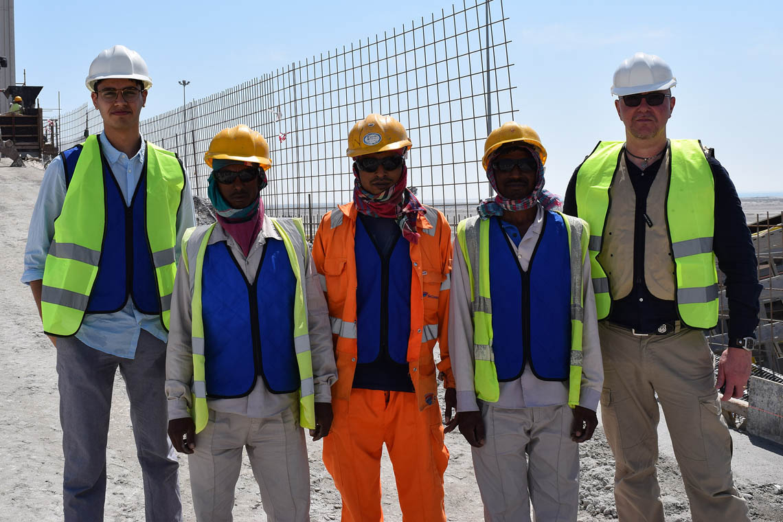 Adam Sheikh and workers demonstrate the cooling vests