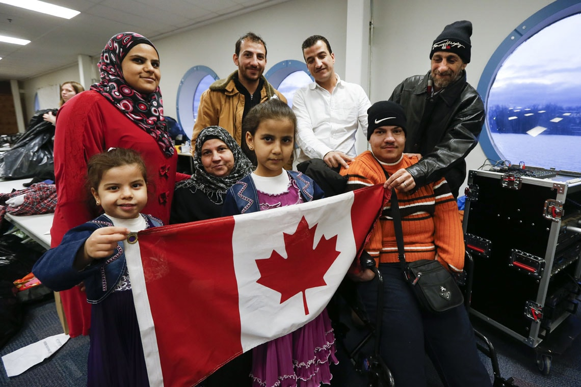 Syrian refugee family holding a Canadian flag