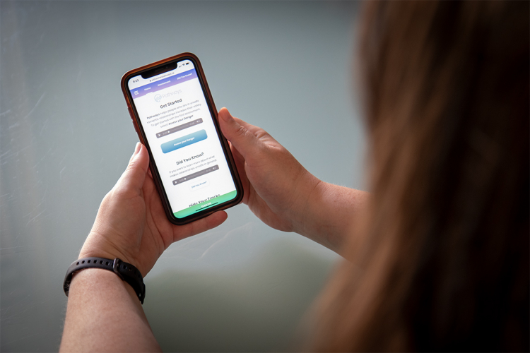 A woman looks at a support app on her phone