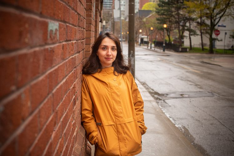 Azadeh Barzideh stands outside her residence, wearing a yellow raincoat