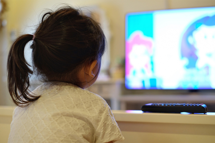 a young asian girl watches tv