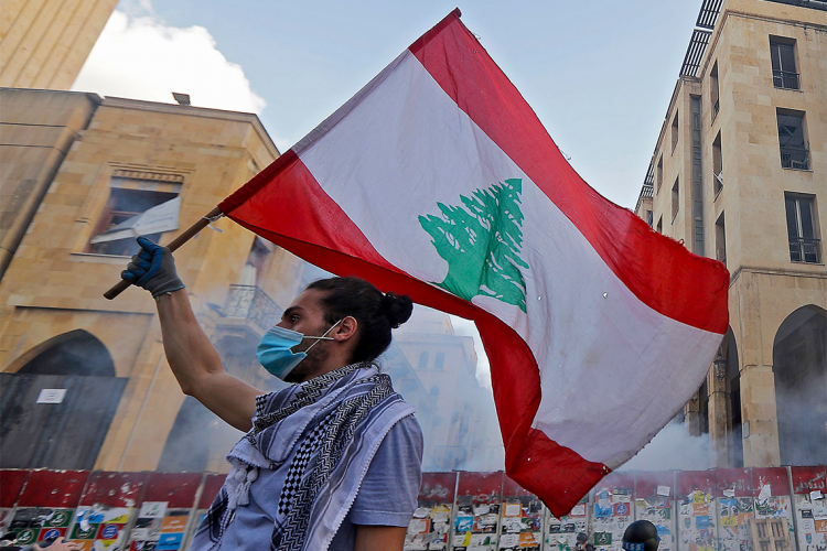 protestor waving a lebanese flag in beirut