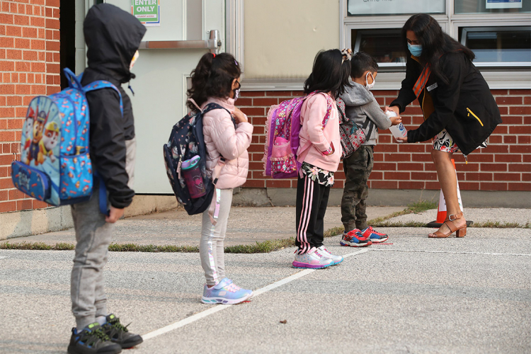 Children line up to sanitize their hands outside of an elementary school in Toronto