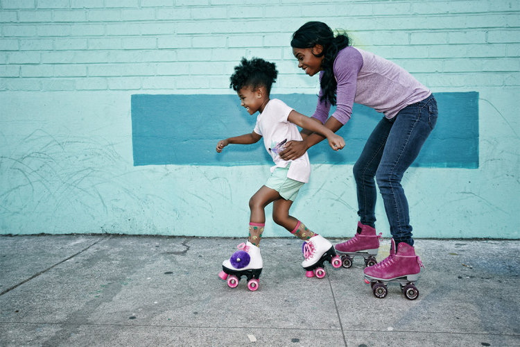 mother helps daughter roller skate