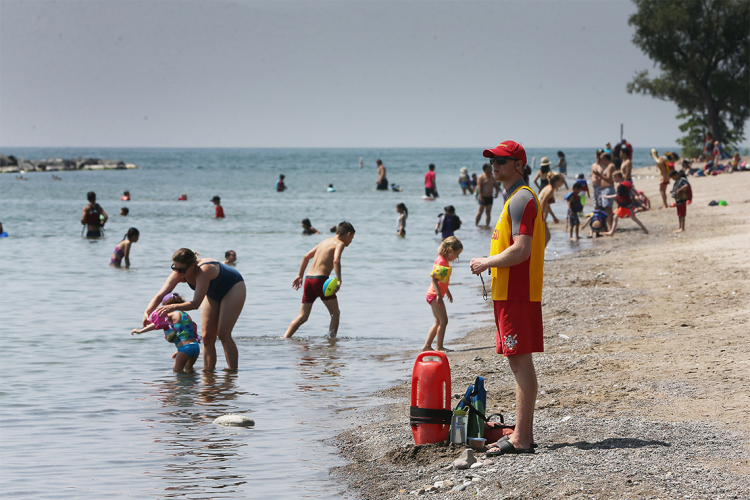 A lifeguard stands watch over swimmers at a Toronto beach