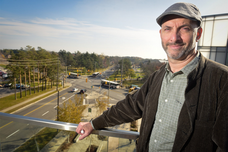 Andre Sorenson on a balcony overlooking a traffic intersection in Scarborough
