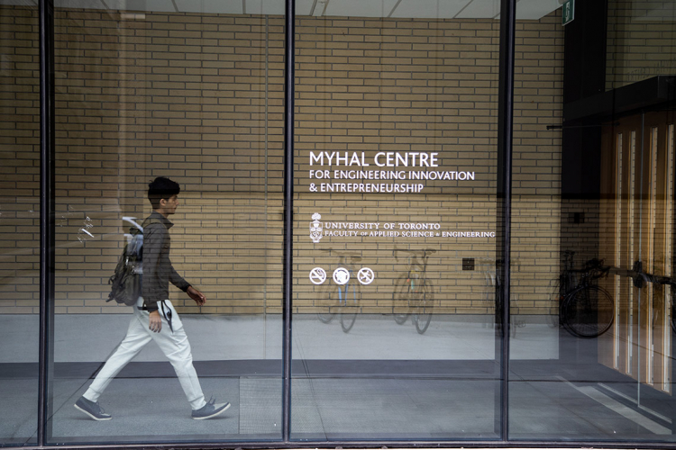 A student walks behind a glass wall at U of T's Myhal Centre