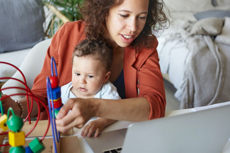 A woman plays with her child while trying to work on her laptop