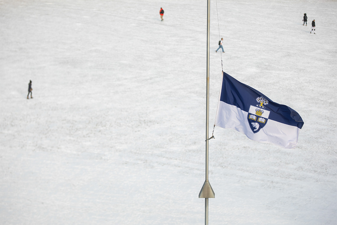 Photo of a U of T flag flying at half mast with a field of snow in the background