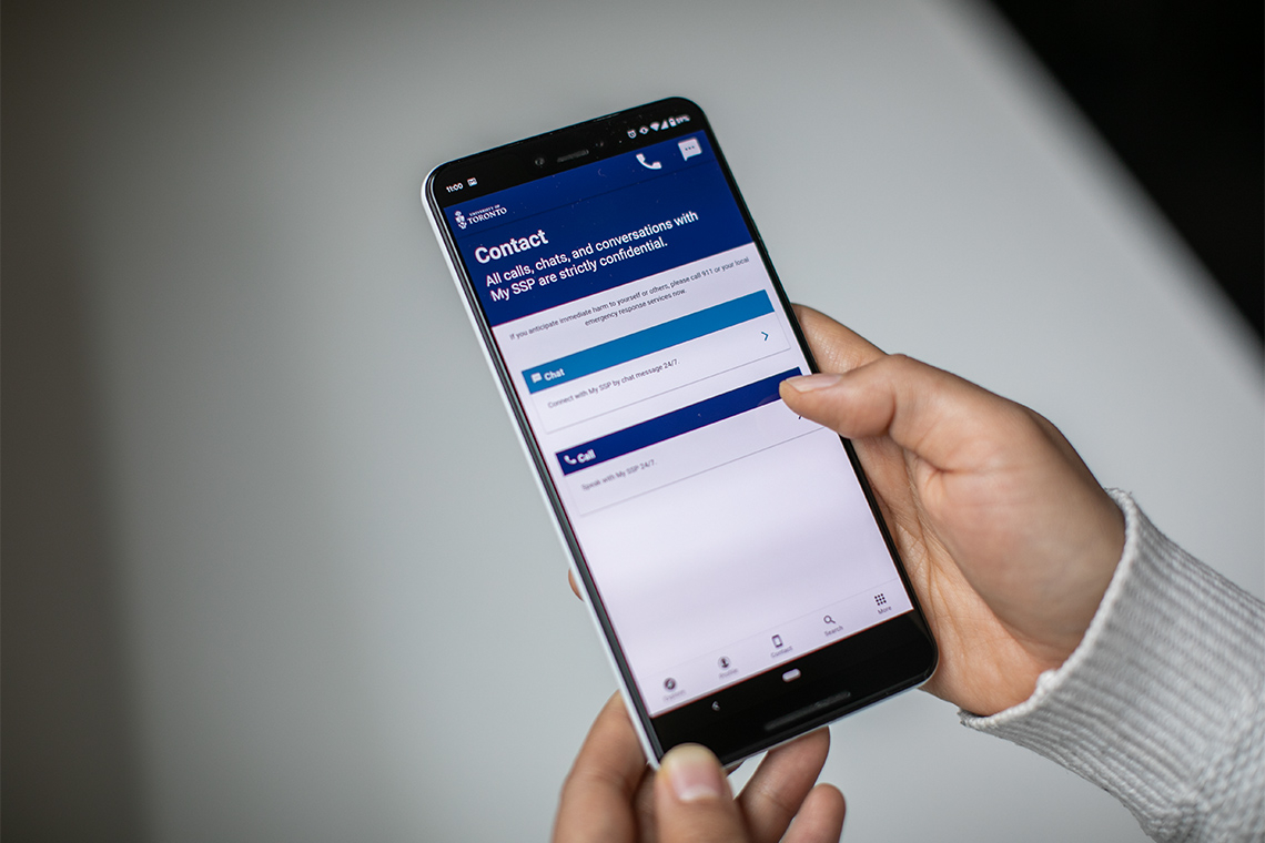 A person holds a smartphone displaying the My SSP app