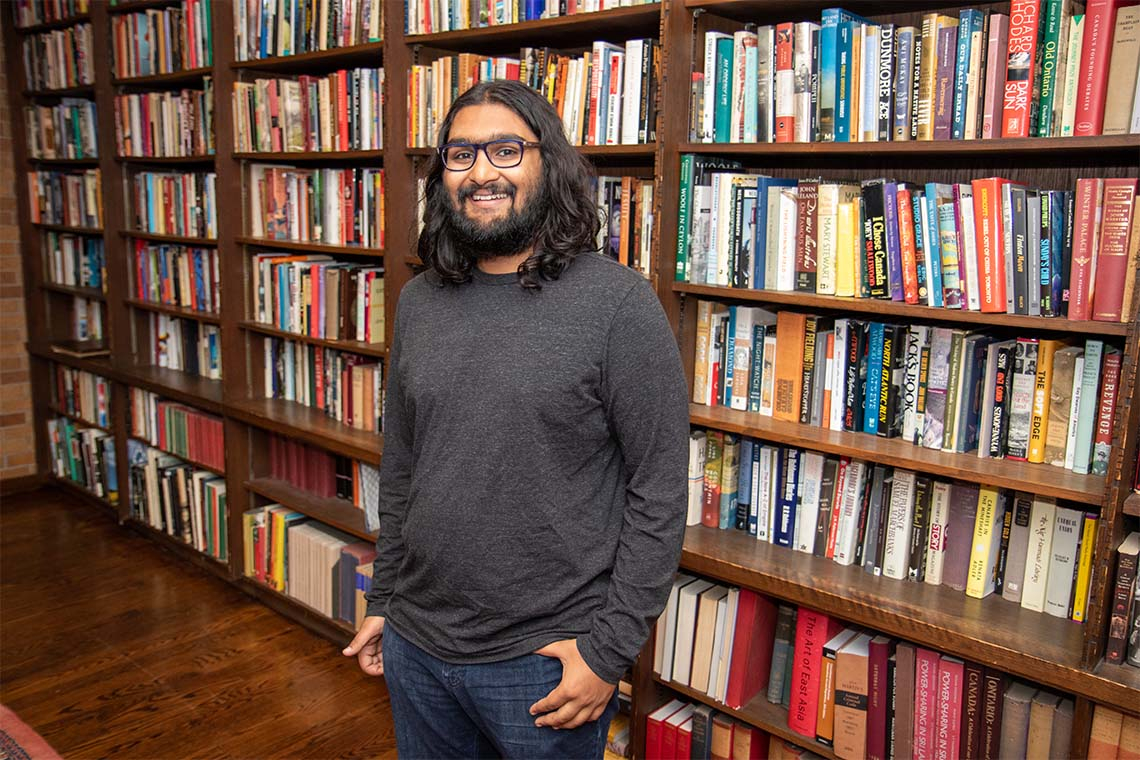Portrait of incoming PhD student Seshu Iyengar shot in front of a row of bookshelves