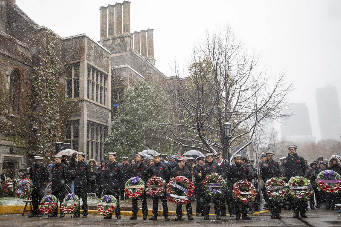 Students hold wreaths outside of Hart House during Remembrance day 2019