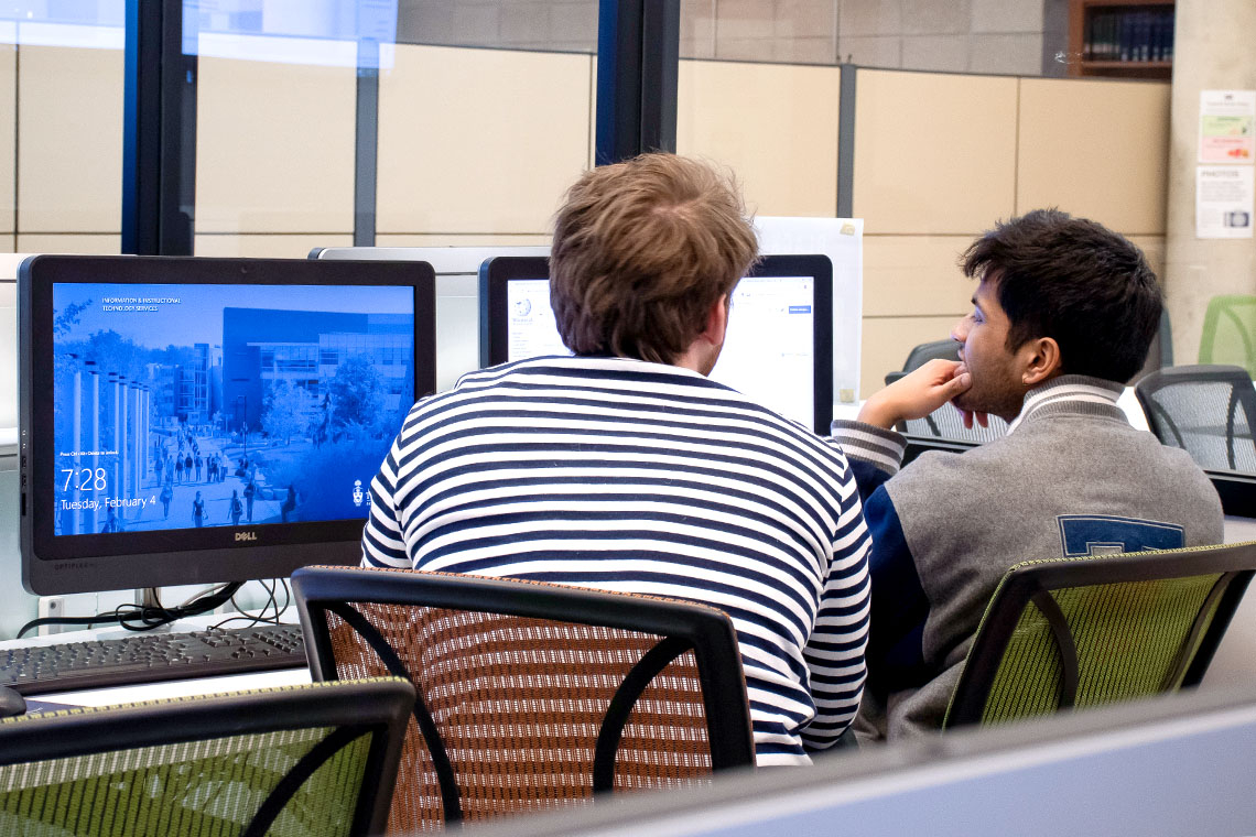 Two students at a computer terminal making edits to a Wikipedia page