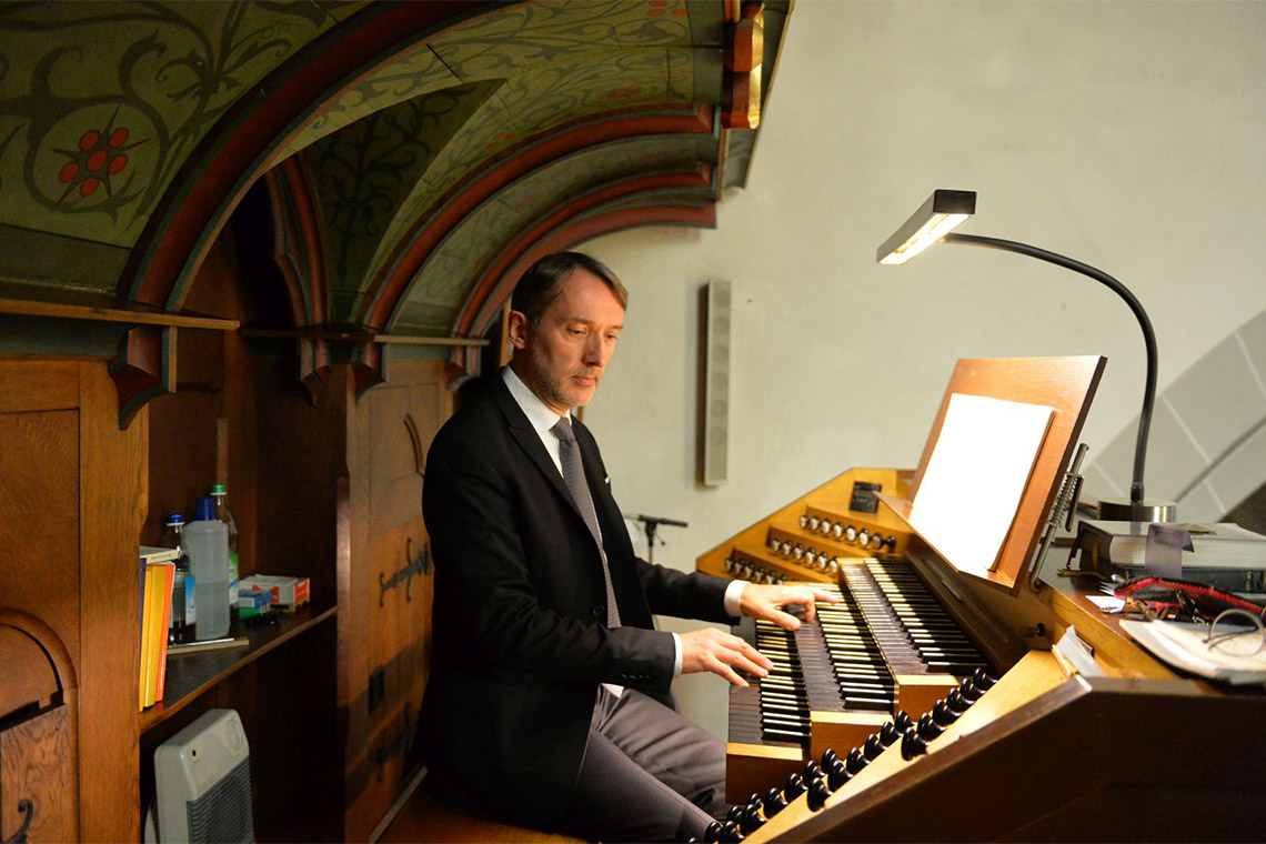 Orgnaist Olivier Latry sits at an organ