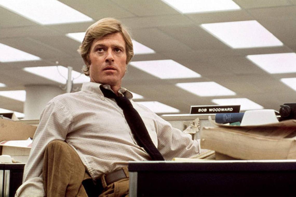 Robert Redford as Bob Woodward sits at a desk in a still from the movie All the President's Men