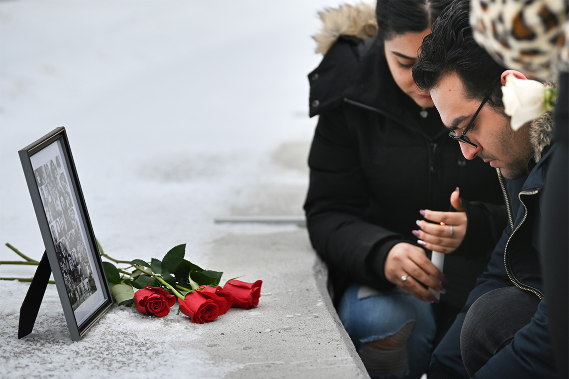 Two U of T students pay their respects in front of a photo of the victims of the plane crash at the U of T Scarborough vigil