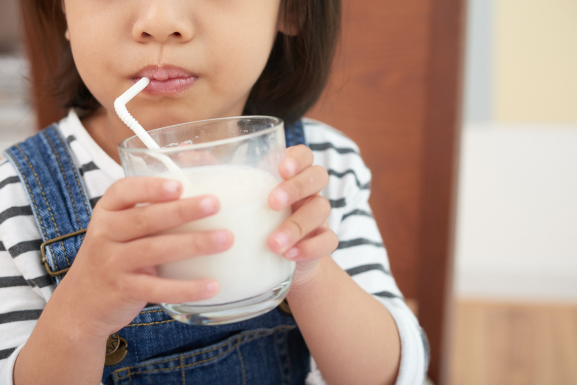 an anonymous young girl is drinking a glass of milk through a straw