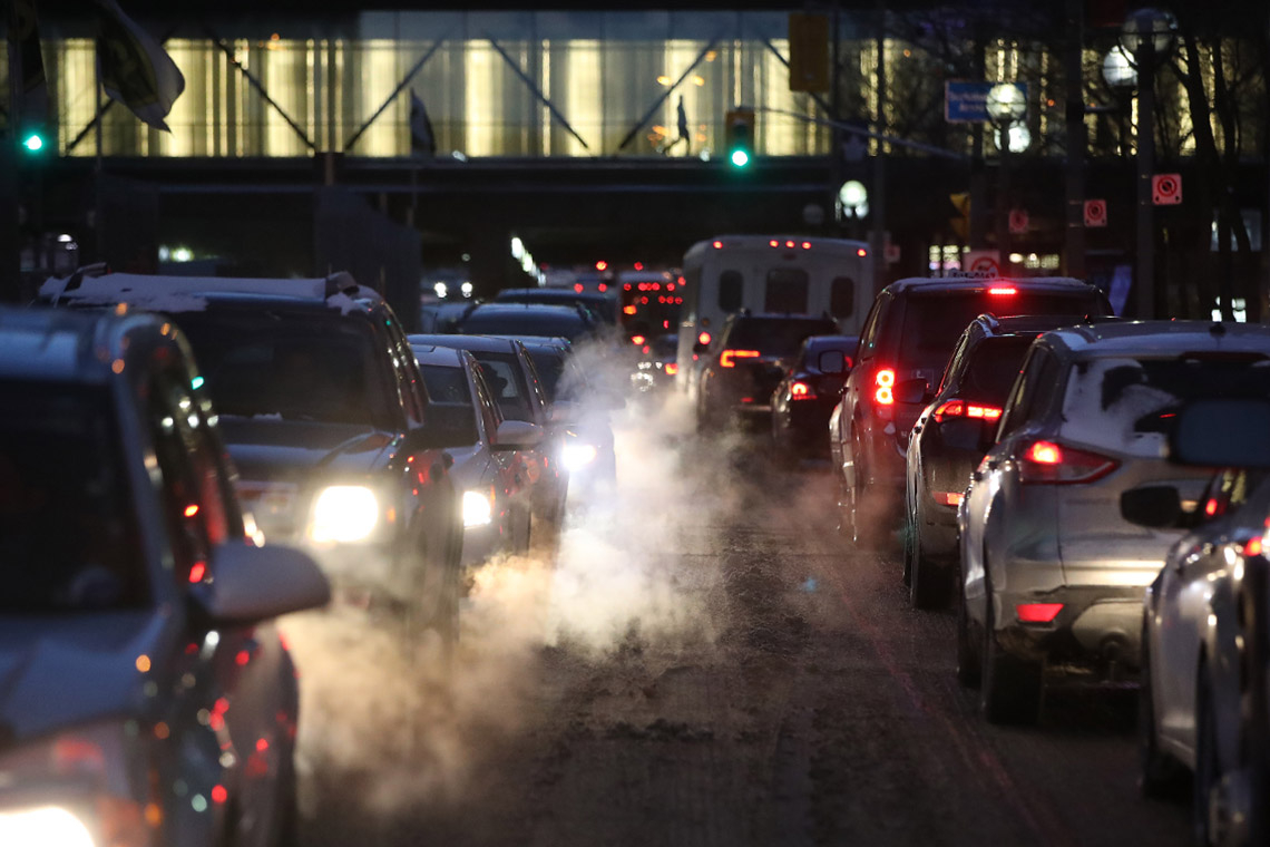 Cars and trucks creep bumper to bumper along a Toronto down street on a winter night