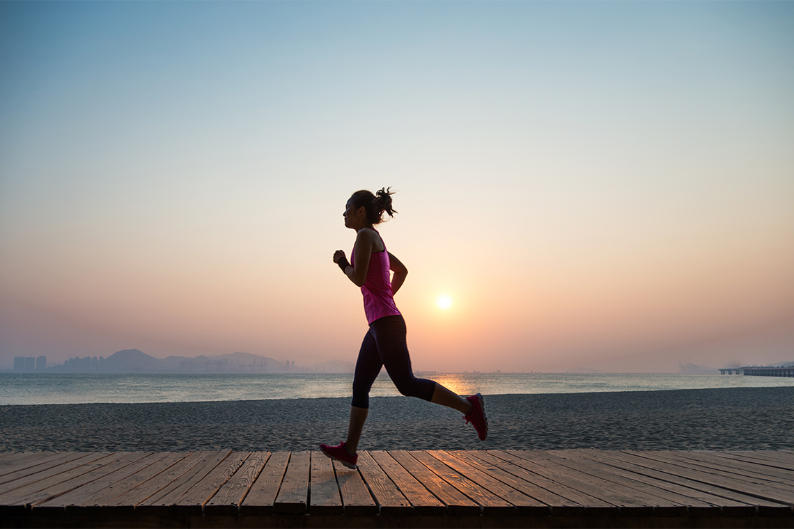 a young woman jogs along the boardwalk at sunrise