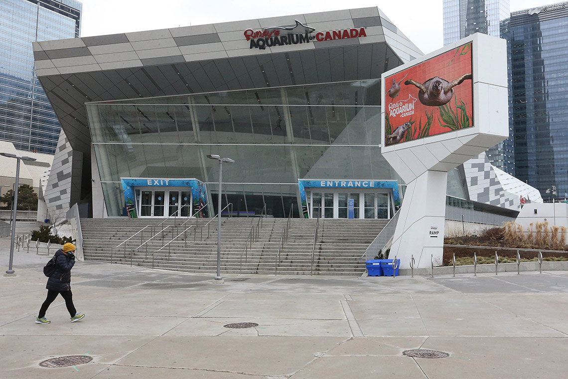 A pedestrian walks in front of an empty Ripley's Aquarium in downtown Toronto