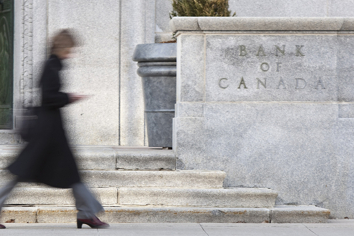 A woman walks past the front entrance of the bank of canada