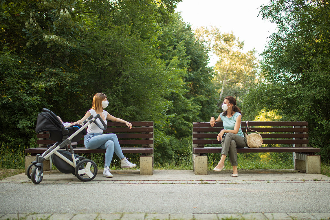 Two women, socially distanced, having a conversation in a park with surgical masks on