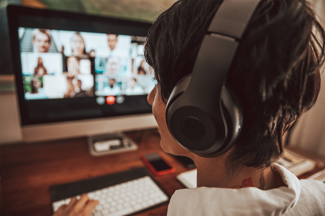 A person wears headphones while participating in a group video conference call