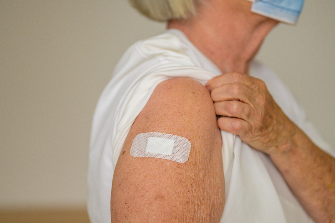 an elderly woman with a band aid on her arm after being vaccinated