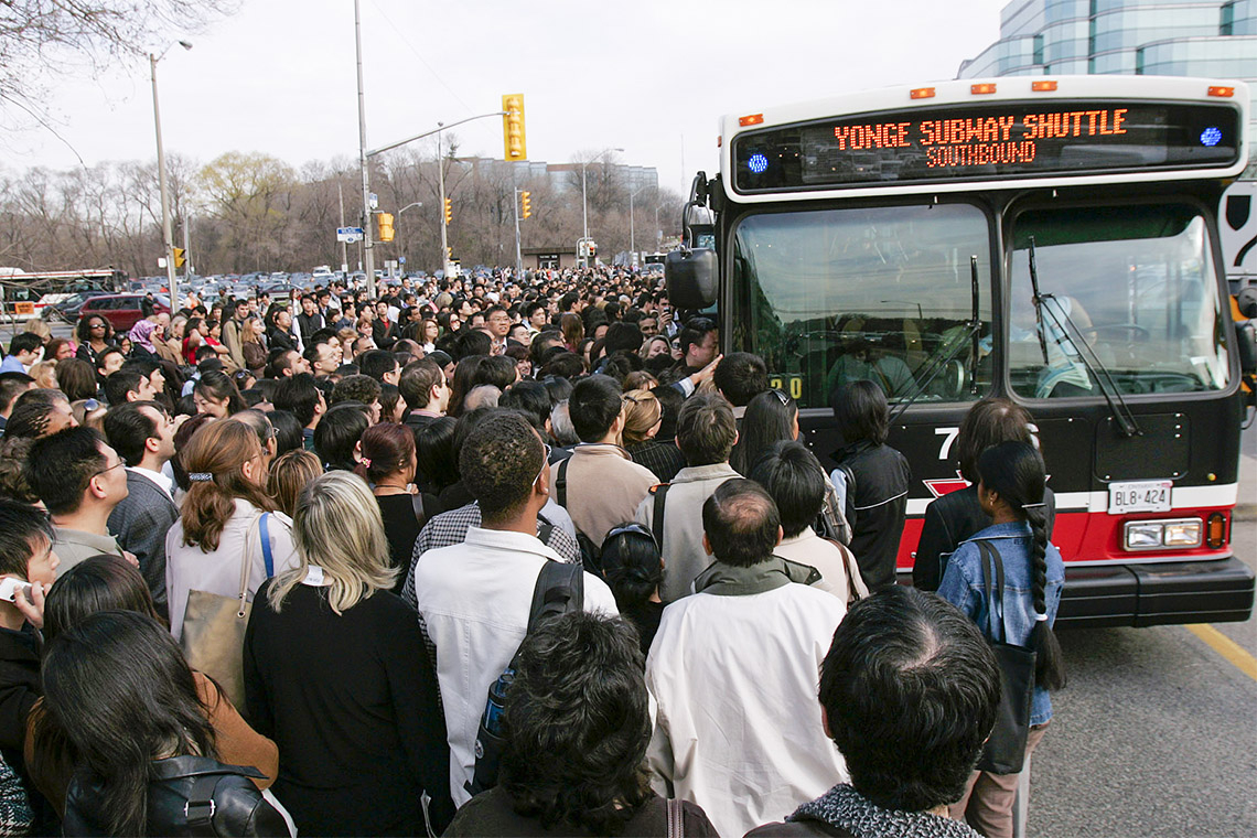 a large crowd of commuters rush a ttc shuttle bus due to a subway closure