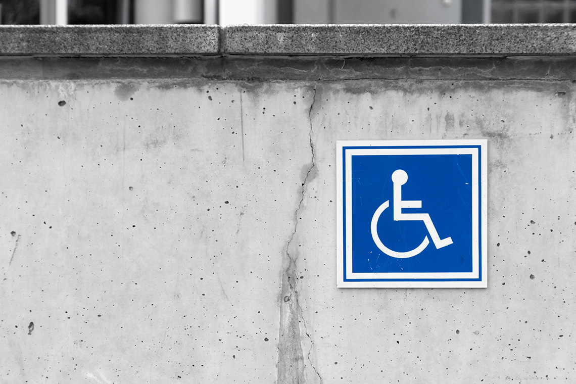 Handicapped parking sign on a concrete wall