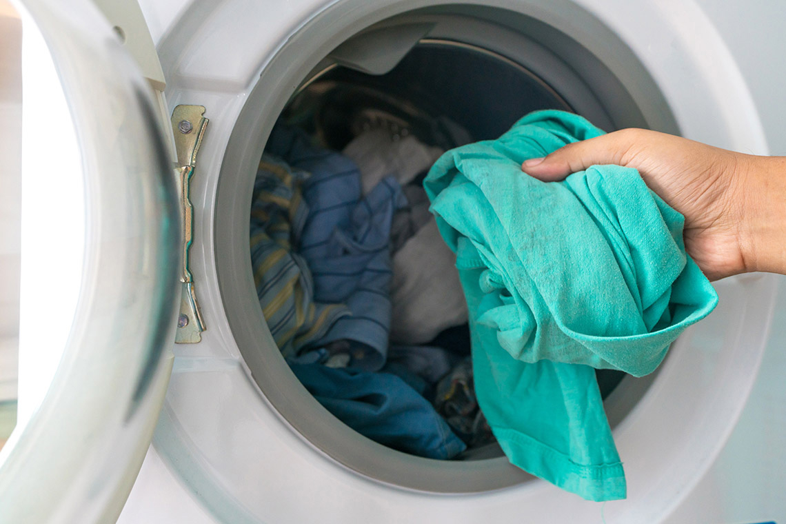 A photo of someone putting clothes into a washing machine