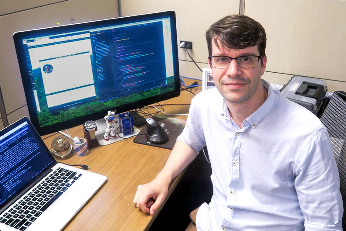 Photo of Jack Jamieson sitting at a desk with two computers