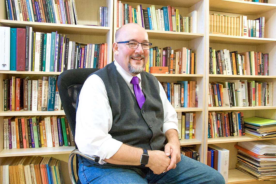Portrait of Kevin White sitting in front of a bookcase